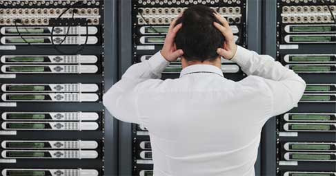 Person in front of server rack holding hands to head
